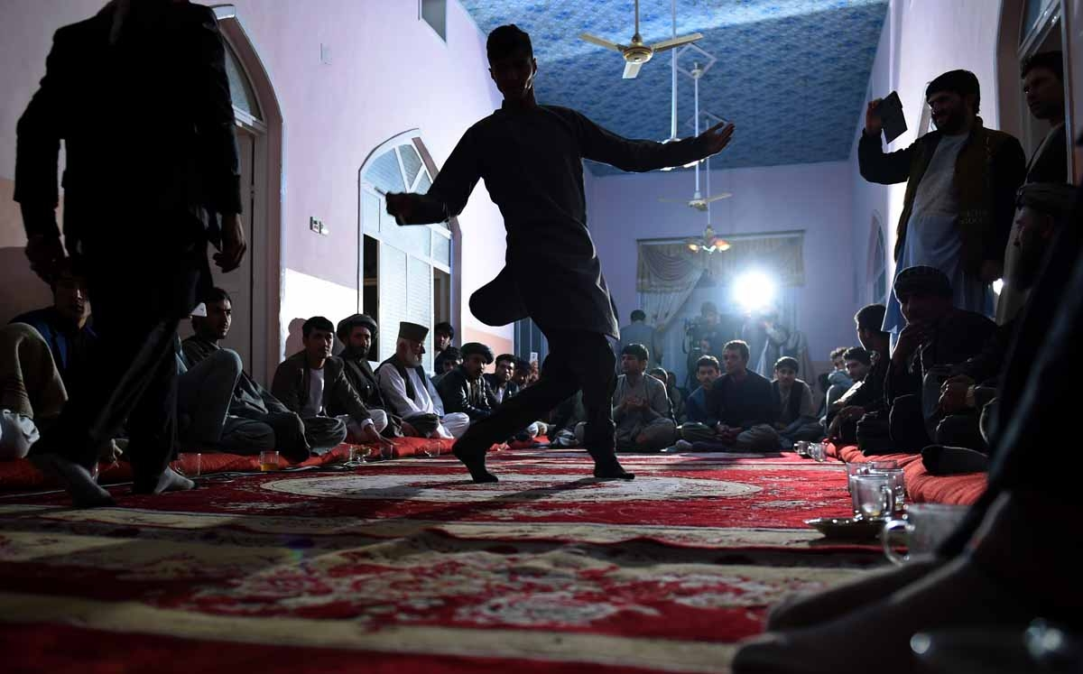 In this photograph taken on October 18, 2015, Afghan men dance in a wedding ceremony inside a house at Khoja Paytakht in Maimana, the capital of the northern province of Faryab.