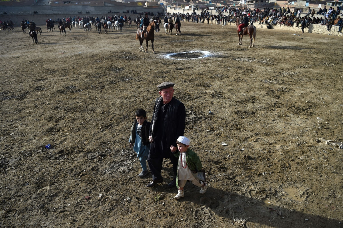 This photo taken on December 1, 2017 shows an Afghan man walking with children as horsemen compete in the traditional sport of buzkashi on the outskirts of Kabul.