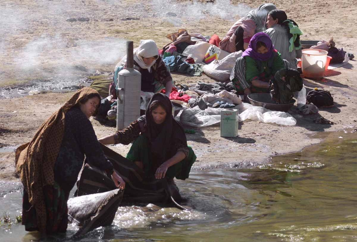 Afghani women with uncovered faces wash their clothes on the bank of Kabul river 15 November 2001. The Northern Alliance, which swept into Kabul 13 November,
