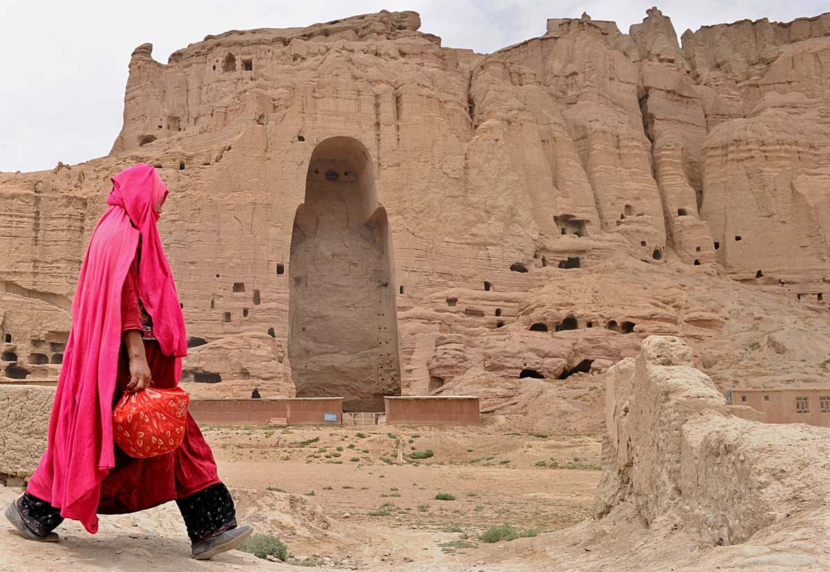 In this file photo taken on August 1, 2010 a Hazara Afghan woman walks past the ruins of the ancient Buddha statues that once stood in the city of Bamiyan. Agence France-Presse's chief photographer in Kabul, Shah Marai, was killed April 30