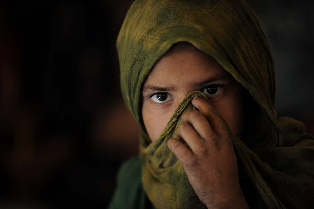 An Afghan Kuchi girl covers her face as she attends a class in a tent in front of the ruins of the Darlaman Palace which was destroyed during the civil war, on the outskirts of Kabul on October 27, 2010.