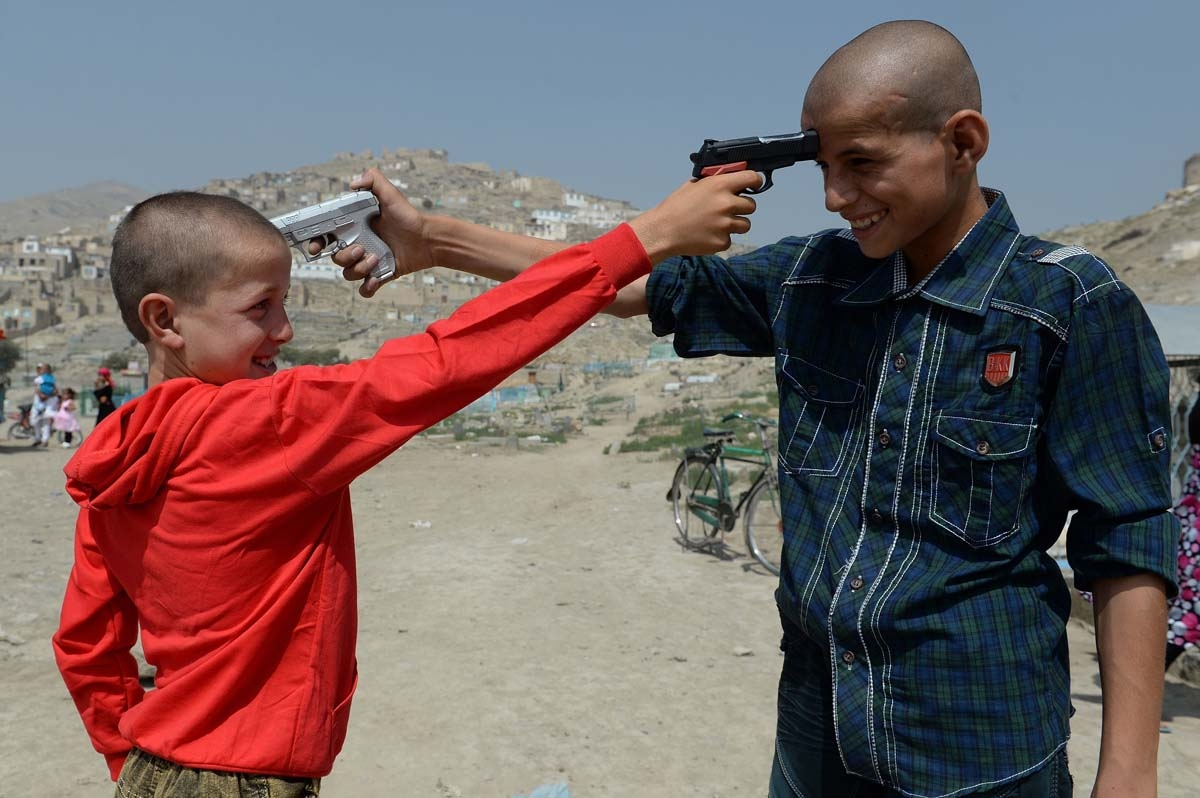 Afghan children play with plastic toy guns in Kabul on August 8, 2013. Civilian casualties in the Afghan war rose 23 percent in the first half of this year due to Taliban attacks and increased fighting between insurgents and government forces, the UN said