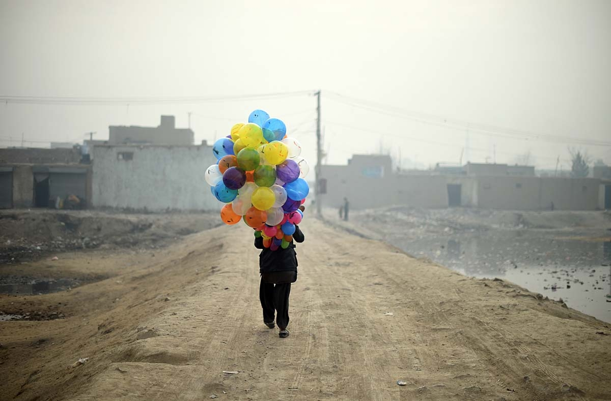 Afghan balloon vendor Arash, 19, waits for customers as he walks through a neighbourhood in Kabul on January 12, 2015. Arash sells balloons for 5 Afghani, which is the equivalent to less then one US cent, makes around 4 USD per day when business is good.