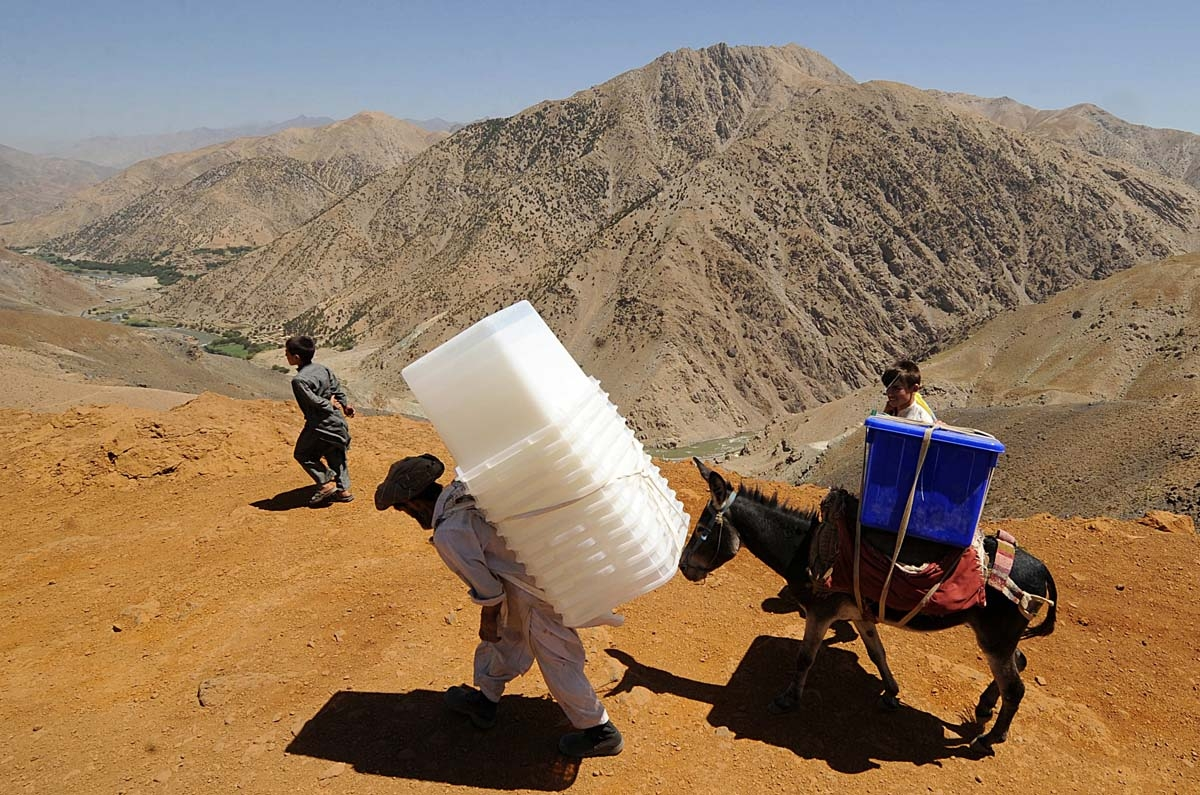 An Afghan man carries ballot boxes as he guides his donkey carrying election supplies in the rugged mountains of the Panjshir valley on August 19, 2009.
