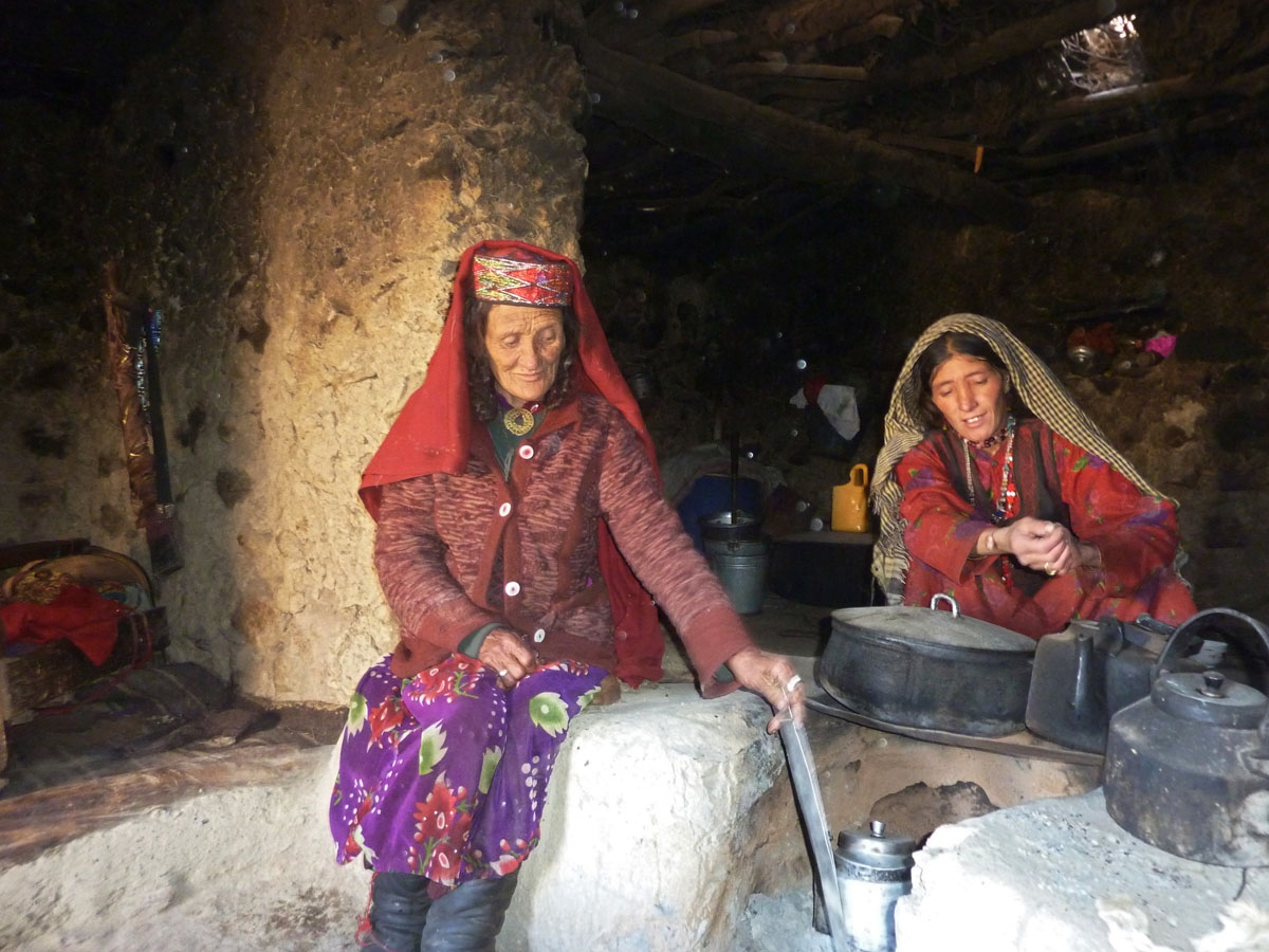 Sultan Begium (L) and her daughter-in-law prepare food inside their mud home.