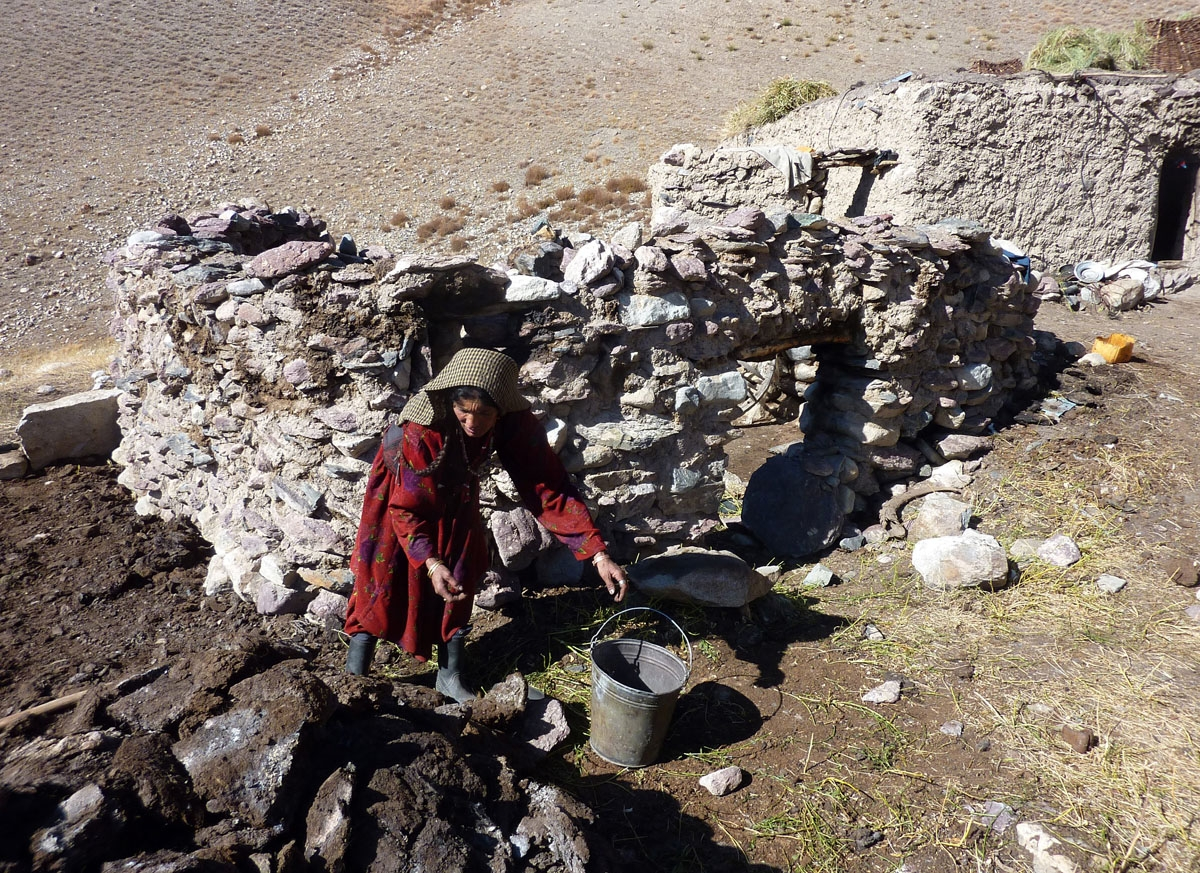 This photograph taken on October 10, 2017 shows Afghan Wakhi nomadic woman Nobot Begium collecting yak dungs that is using for fire fuel outside an animal pen in the Wakhan Corridor in Afghanistan.