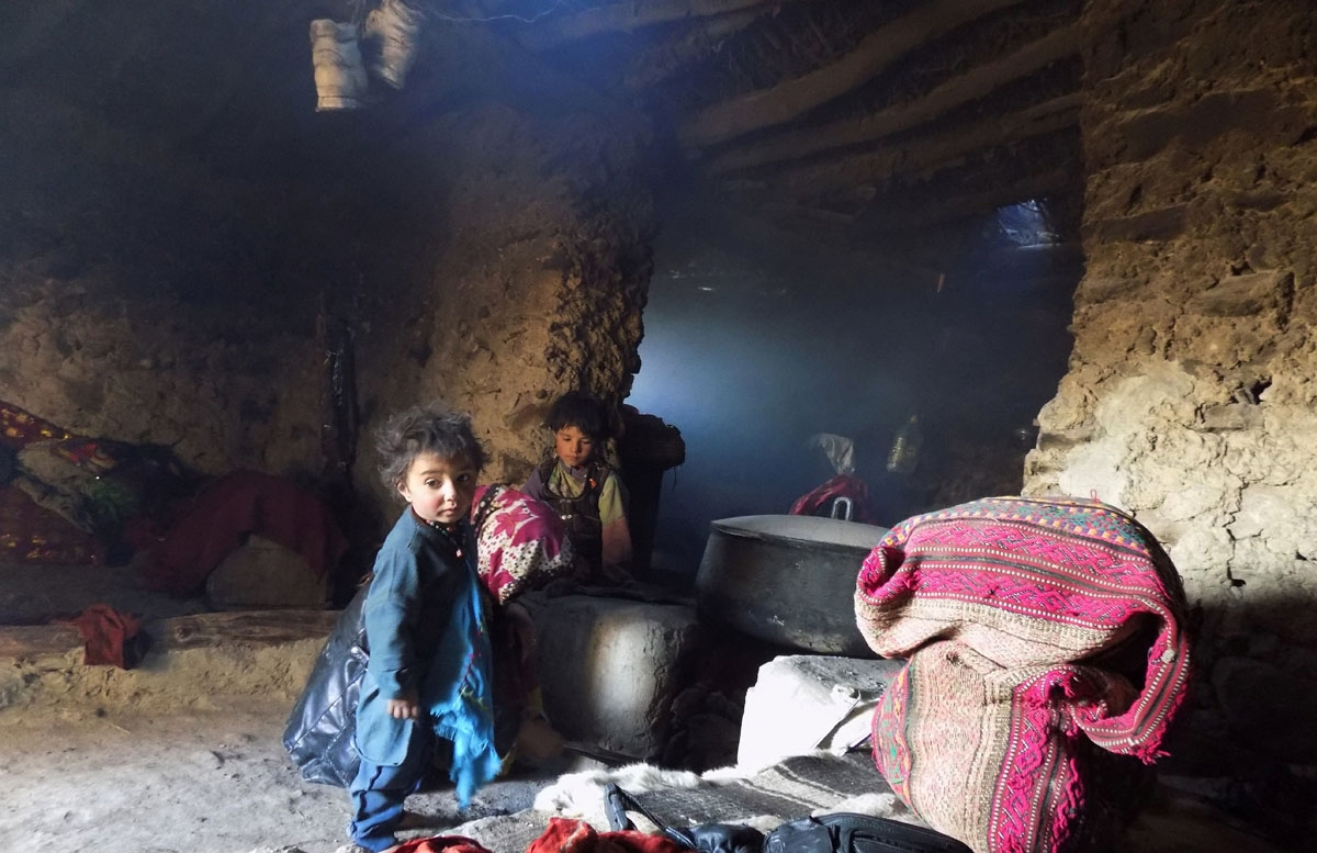 This photograph taken on October 7, 2017 shows Afghan Wakhi nomad children by a stove inside their mud home in the Wakhan Corridor in Afghanistan.