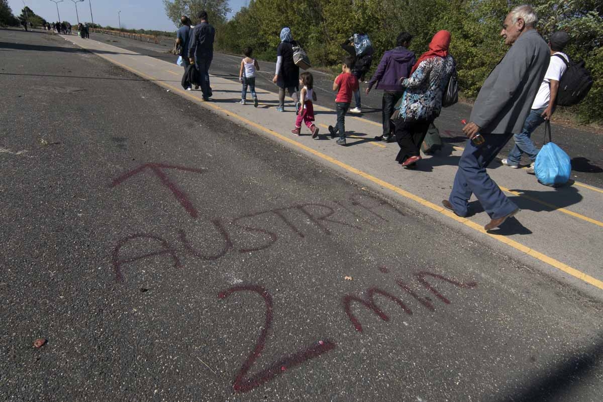 'Austria 2 min' ('Austria two minutes') is written on the ground near a temporary bus station as migrants arrive at the Hungarian-Austrian border on September 12, 2015, near Nickelsdorf, eastern Austria.