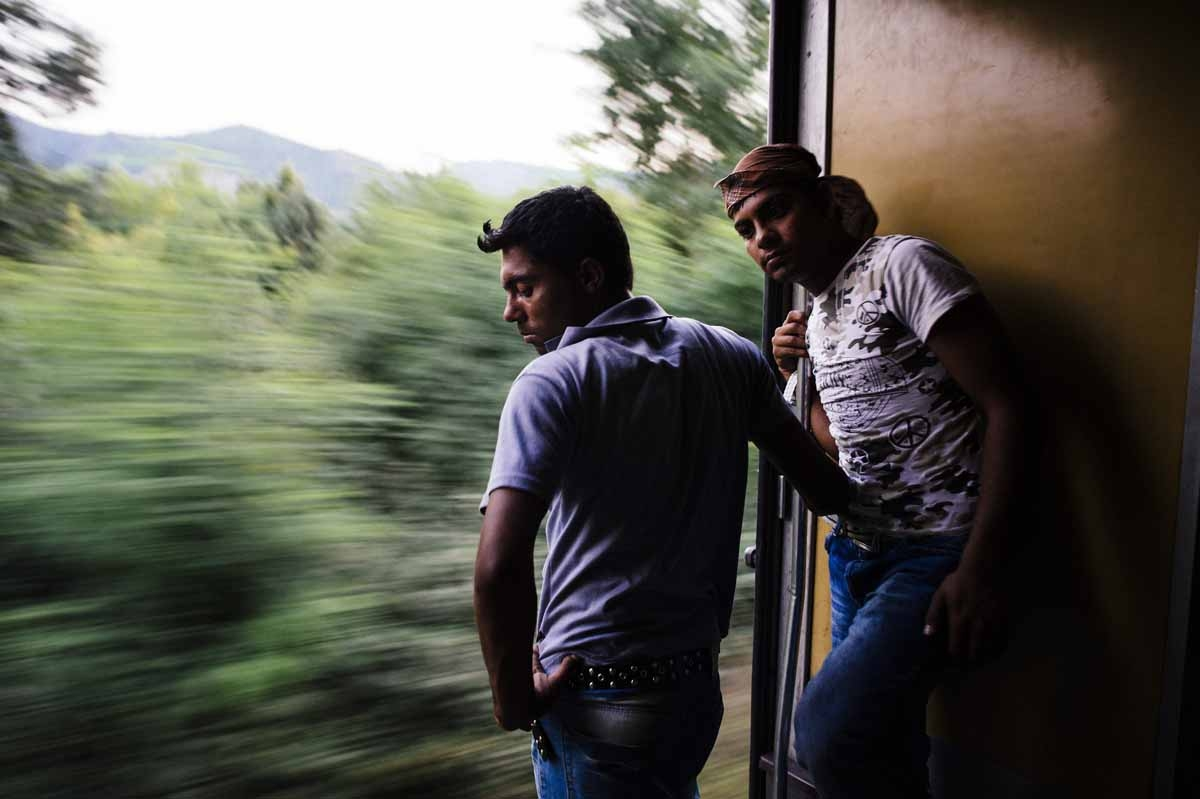 Migrants look out the open door of a train carriage heading north from Gevgelija to Tabanovce, at the border with Serbia on July 27, 2015.
