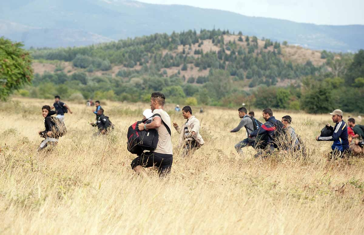 Migrants run through a field after they jumped a fence at the border line at between Greece and Macedonia near the town of Gevgelija on August 22, 2015.