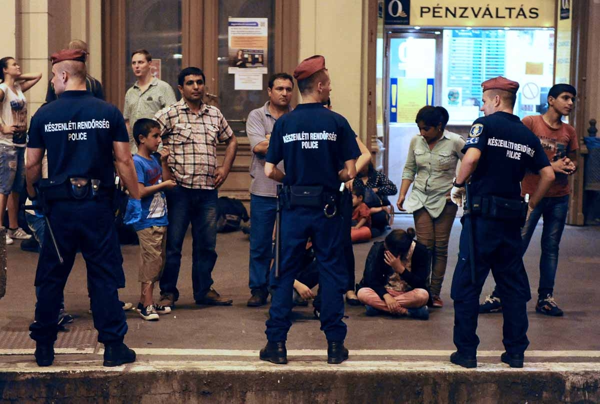 Migrants wait on a platform of the Eastern (Keleti) railway station of Budapest behind of a line of the local police on August 31, 2015, as the last train left in direction of Austria and Germany.