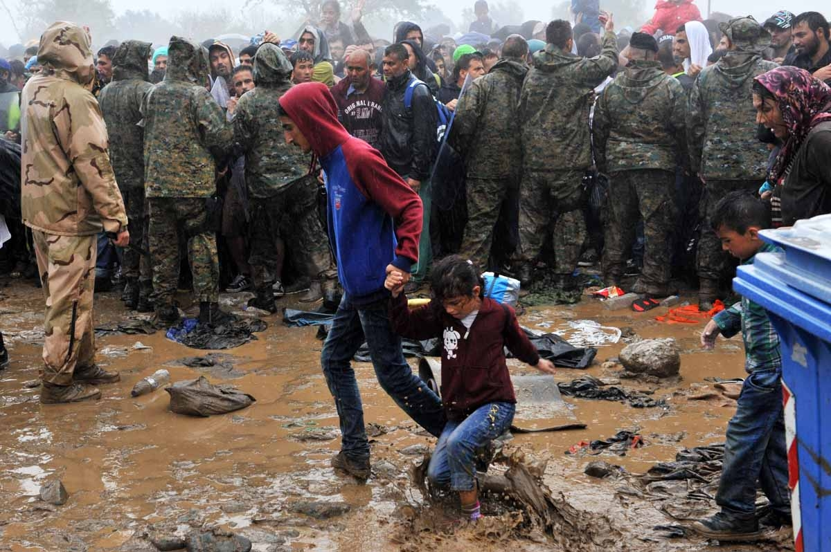 Migrants and refugees wait in the mud and under the rain to cross the Greek-Macedonian border near the village of Idomeni, in northern Greece on September 10, 2015.