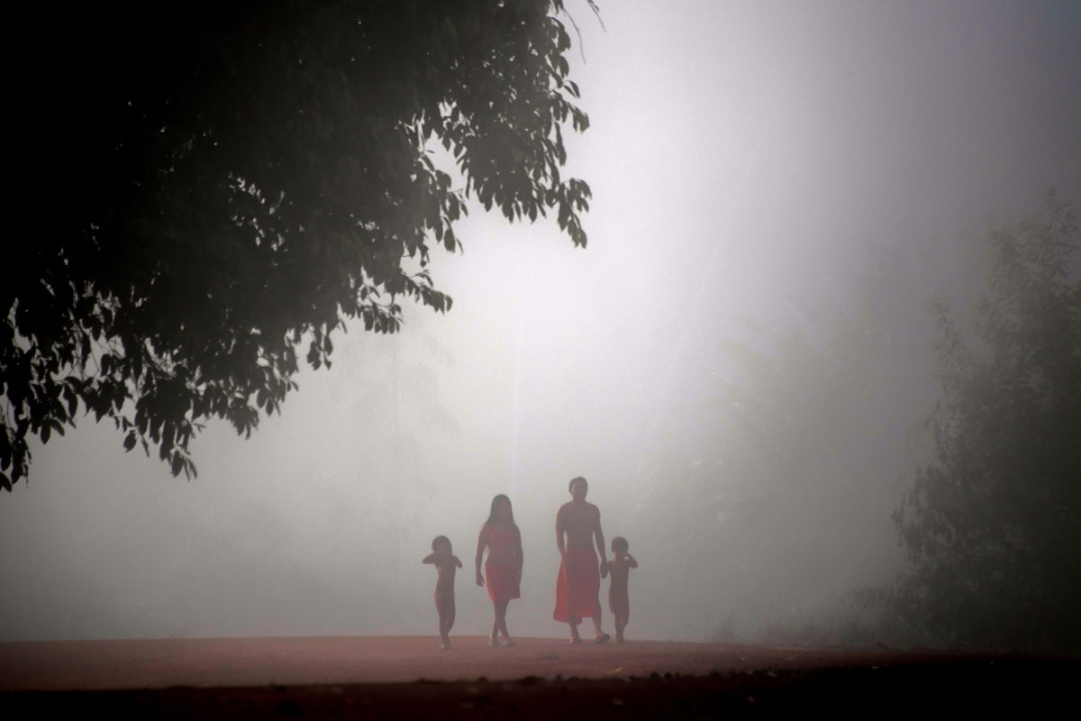 Jawaruwa Waiapi and his family walk amidst fog, early in the morning, at the  Manilha village in the Waiapi indigenous reserve in Amapa state in Brazil on October 13, 2017.