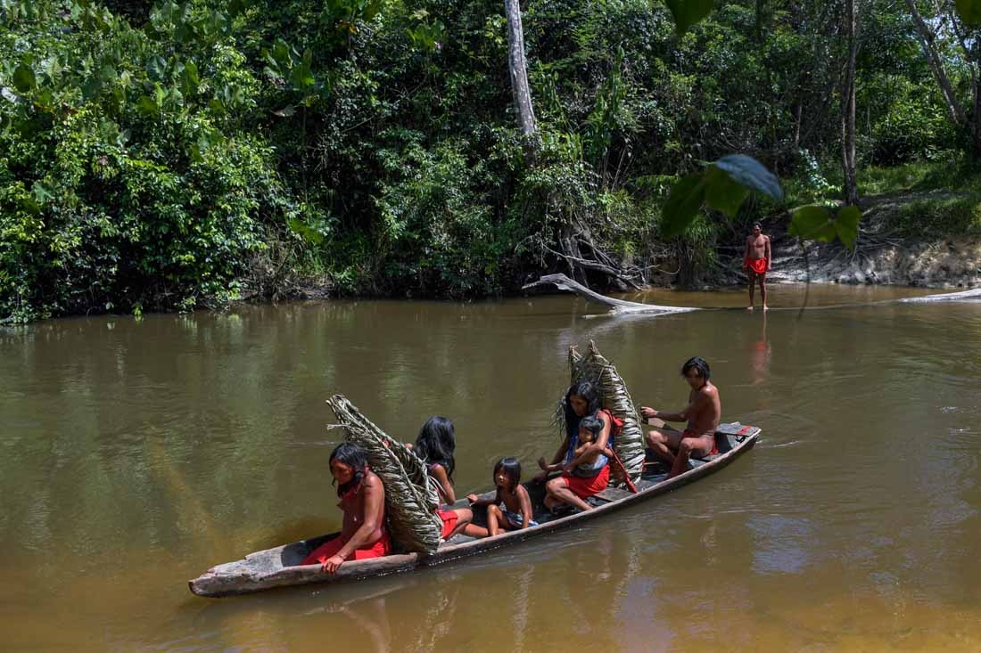 Waiapi people cross the Feliz river by barge, to go to harvest manioc to prepare Caxiri, a craft beer made with Manioc, imbibed daily by men, women and children when is not yet sour yet, at the Waiapi indigenous reserve in Amapa state in Brazil on October