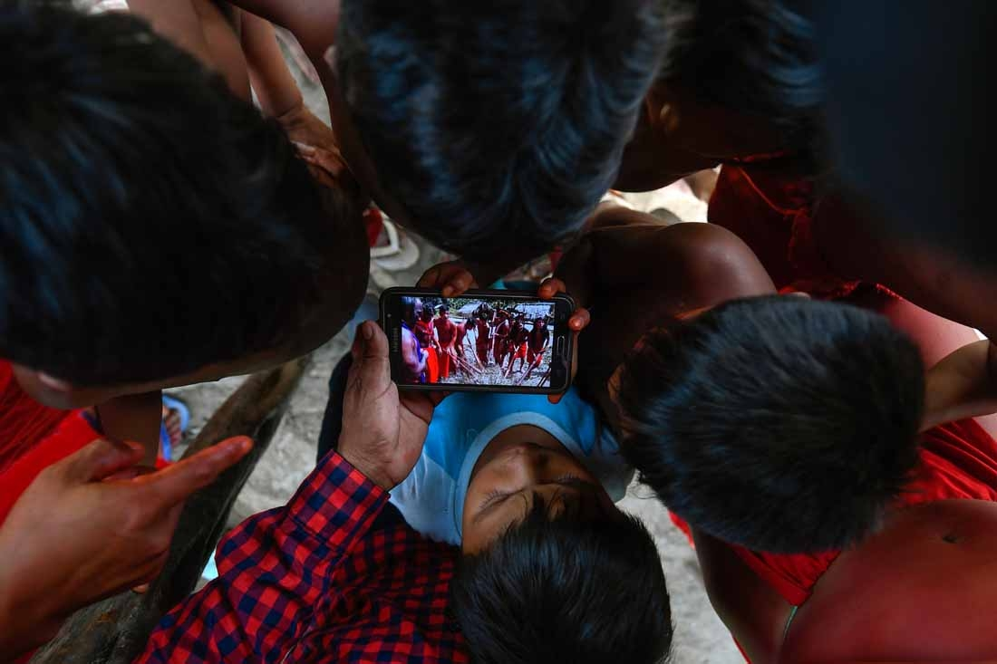 Waiapi children watch a video of a traditional Waiapi dance in a mobile phone at the Manilha village at the indigenous reserve Waiapi in Amapa state in Brazil on October 12, 2017.