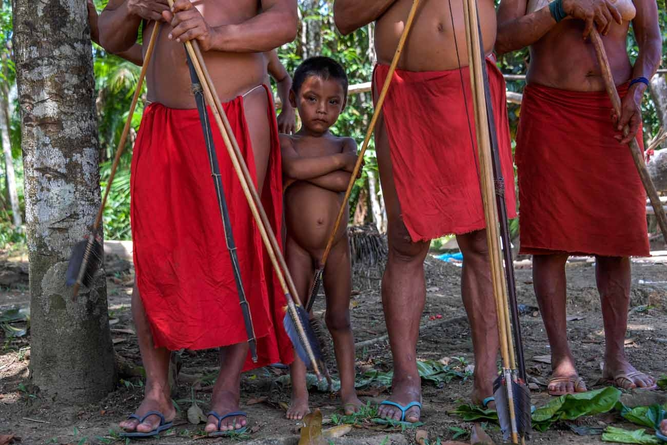 A Waiapi boy stands behind adults at the Pinoty village in Waiapi indigenous reserve in Amapa state in Brazil on October 12, 2017.