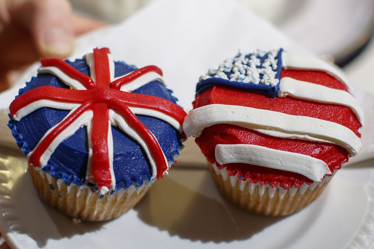A member of staff at the Hummingbird Bakery poses with cupcakes themed with icing depicting the Union Flag and the US flag to mark the upcoming Royal Wedding of Prince Harry and US actress Meghan Markle in central London on May 11, 2018.