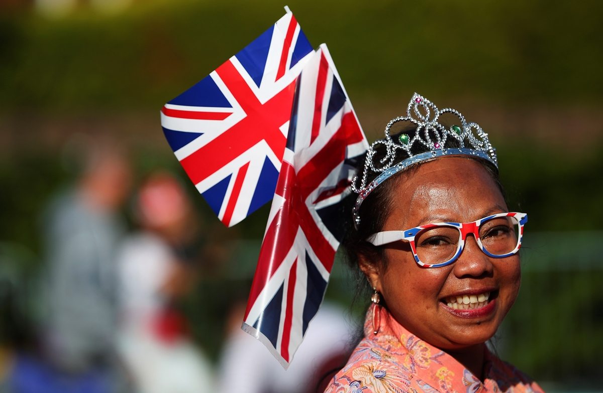 A well-wishers waves a Union flag as she waits on the Long Walk leading to Windsor Castle ahead of the wedding and carriage procession of Britain's Prince Harry and Meghan Markle in Windsor, on May 19, 2018. / AFP PHOTO / POOL / HANNAH MCKAY