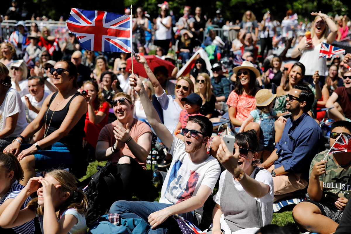 Well-wishers watch a giant screen broadcasting the wedding ceremony of Britain's Prince Harry, Duke of Sussex and Meghan Markle in Windsor, on May 19, 2018. / AFP PHOTO / Tolga AKMEN