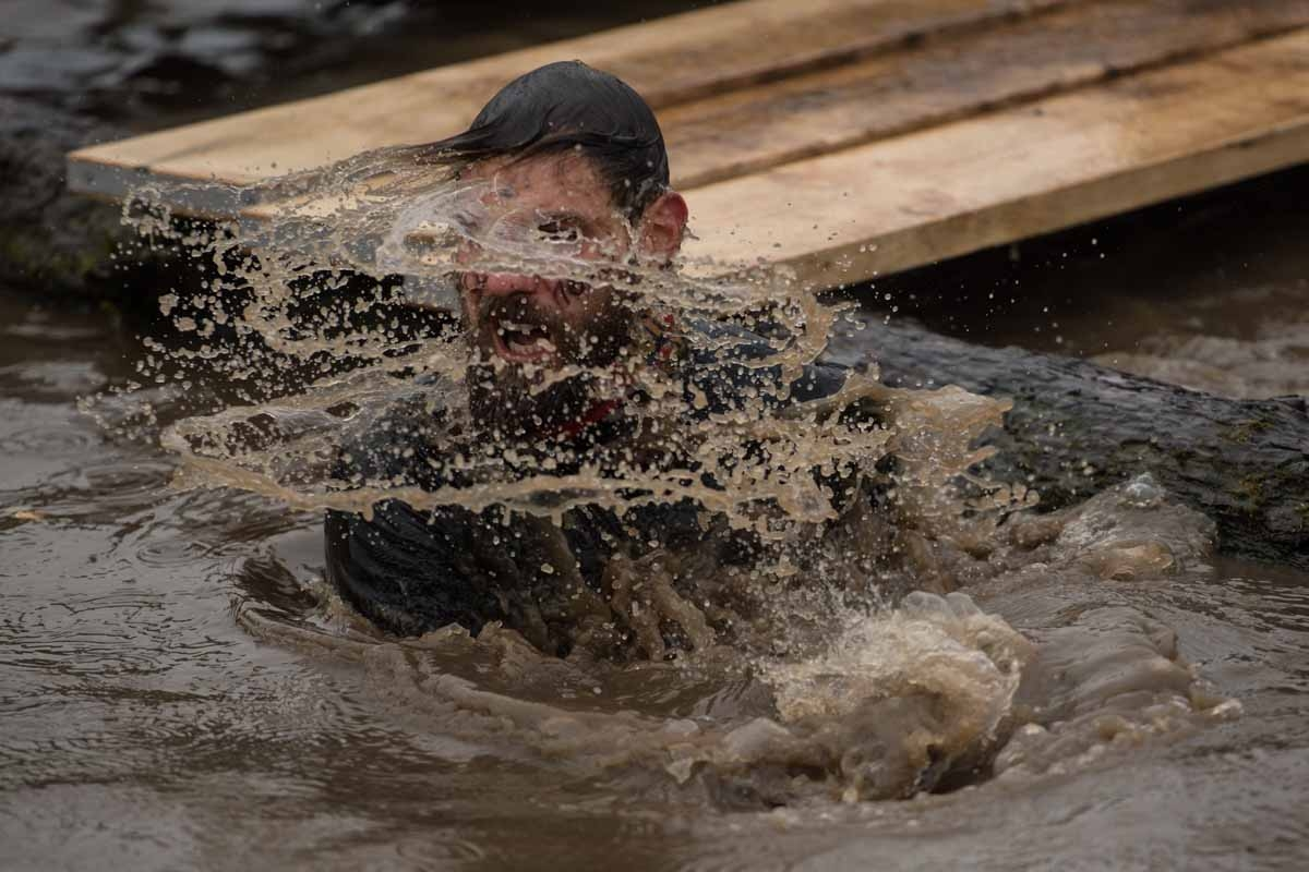 A competitor takes on a water obstacle as he takes part part in the 'Tough Guy' adventure race near Wolverhampton, central England, on January 29, 2017.  The Tough Guy event, which is being held for the final time in its 30th year, challenges thousands of