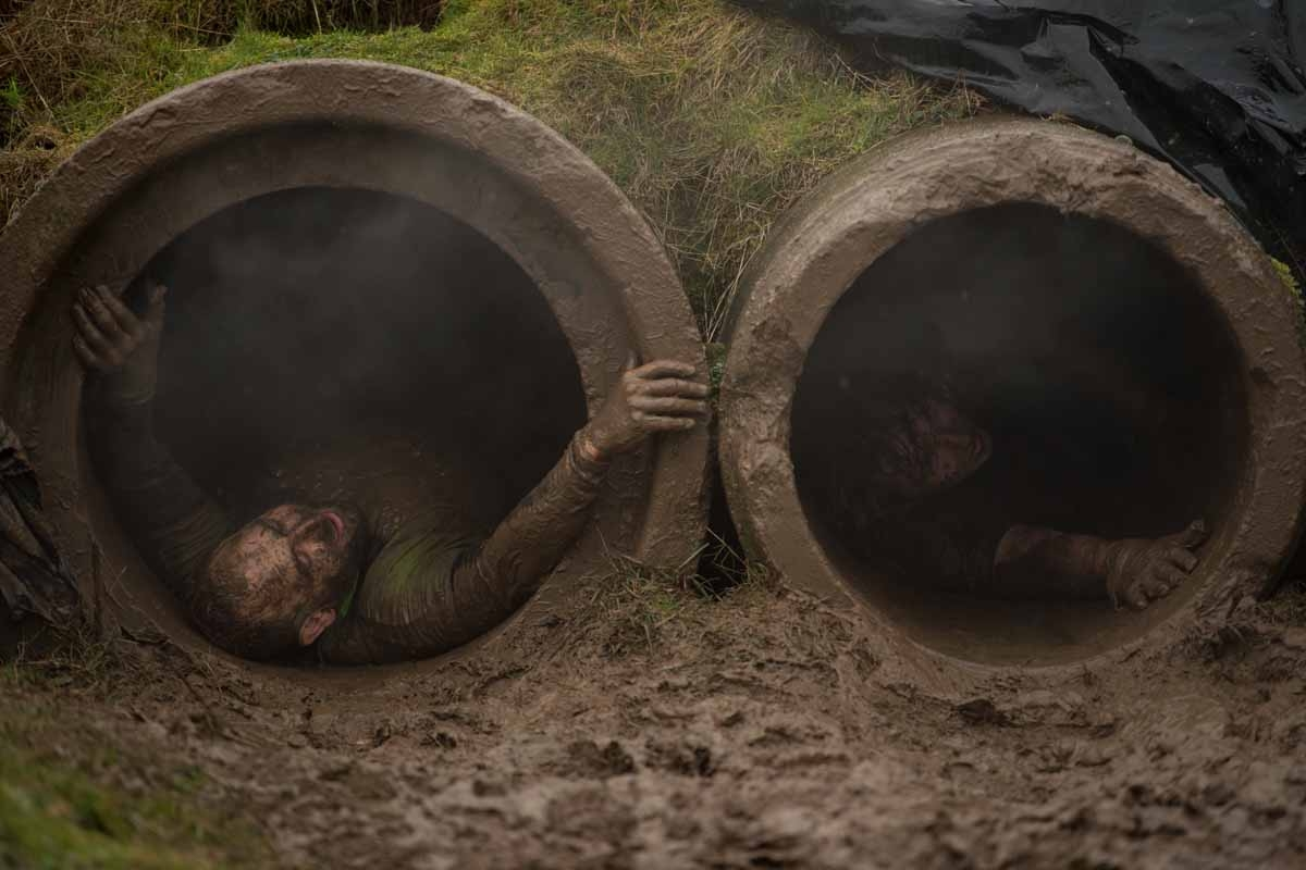 Competitors slide through pipes as they take part in the 'Tough Guy' adventure race near Wolverhampton, central England, on January 29, 2017.  The Tough Guy event, which is being held for the final time in its 30th year, challenges thousands of competitor