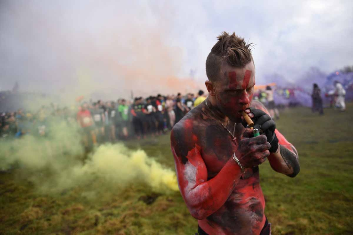 A man with a painted torso lights a cigar before the start of the 'Tough Guy' adventure race near Wolverhampton, West Midlands, on January 29, 2017. The Tough Guy event, which is being held for the final time in its 30th year, challenges thousands of comp