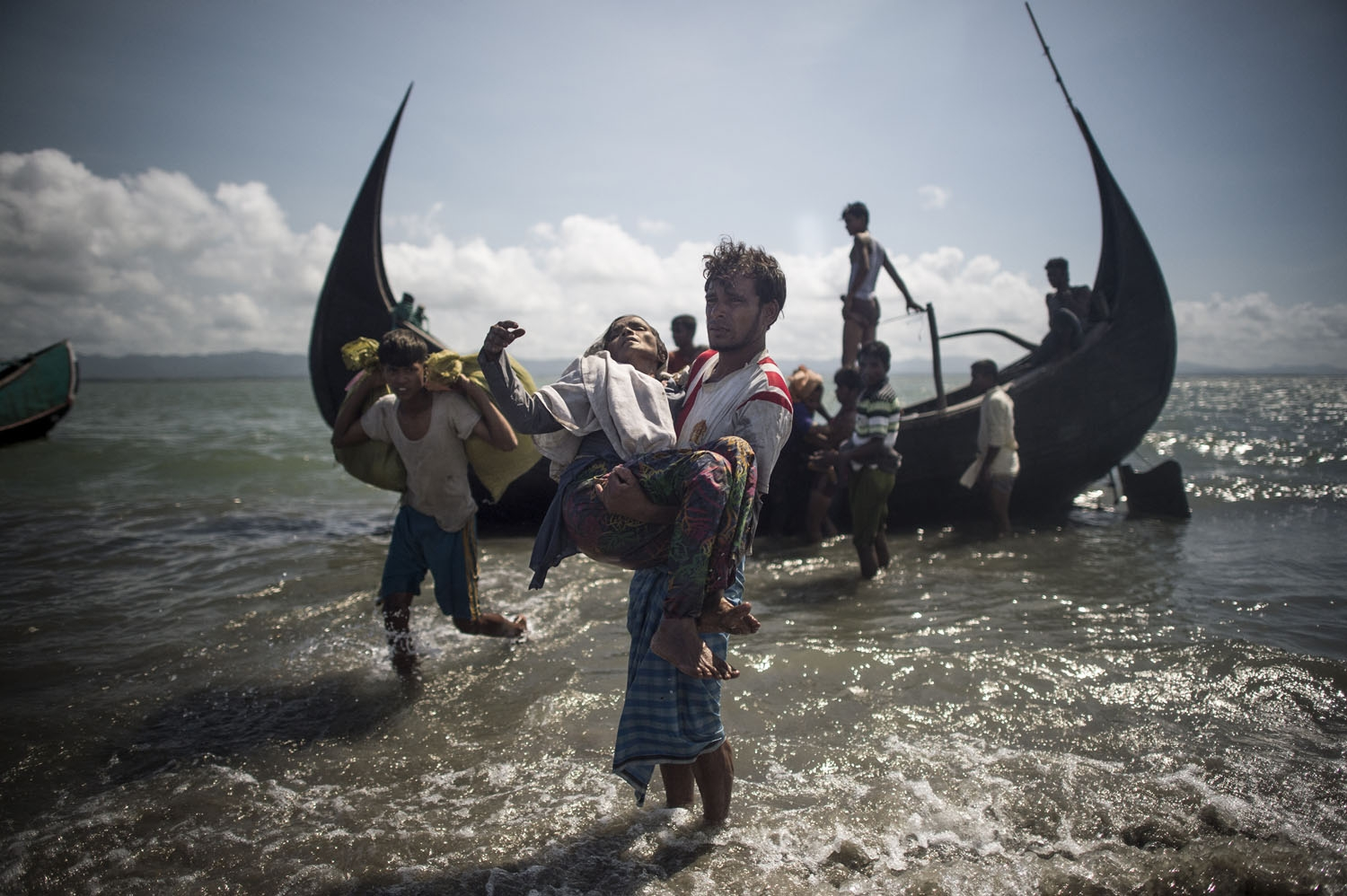 A Bangladeshi man helps Rohingya Muslim refugees to disembark from a boat on the Bangladeshi shoreline of the Naf river after crossing the border from Myanmar in Teknaf on September 30, 2017.