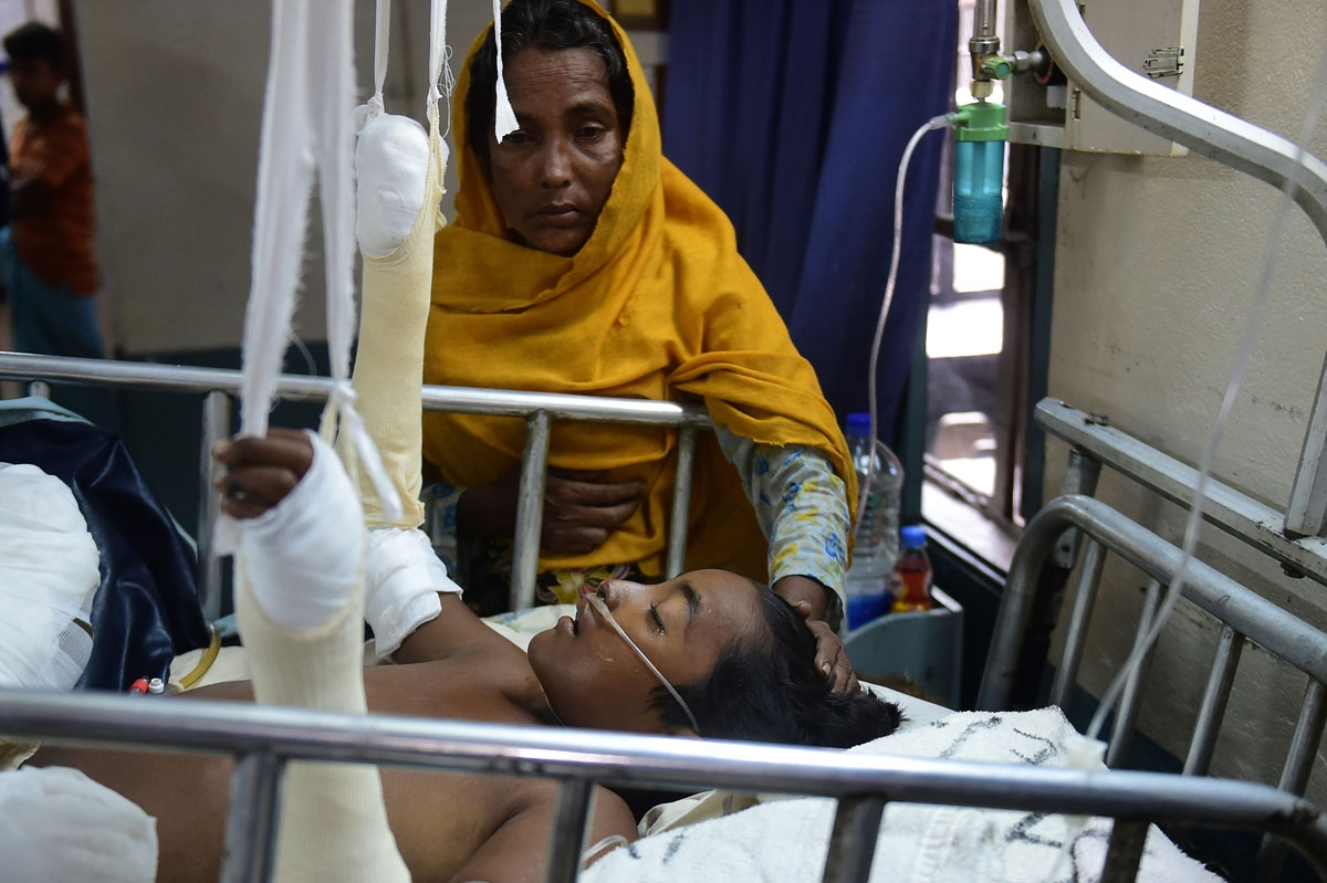 In this picture taken on September 13, 2017, Rohingya Muslim refugee Rashida Begum stands next to her son Azizul Hoque, 15, as he is treated after being injured by a landmine while crossing from Myanmar to Bangladesh, at a hospital in Cox's Bazar.