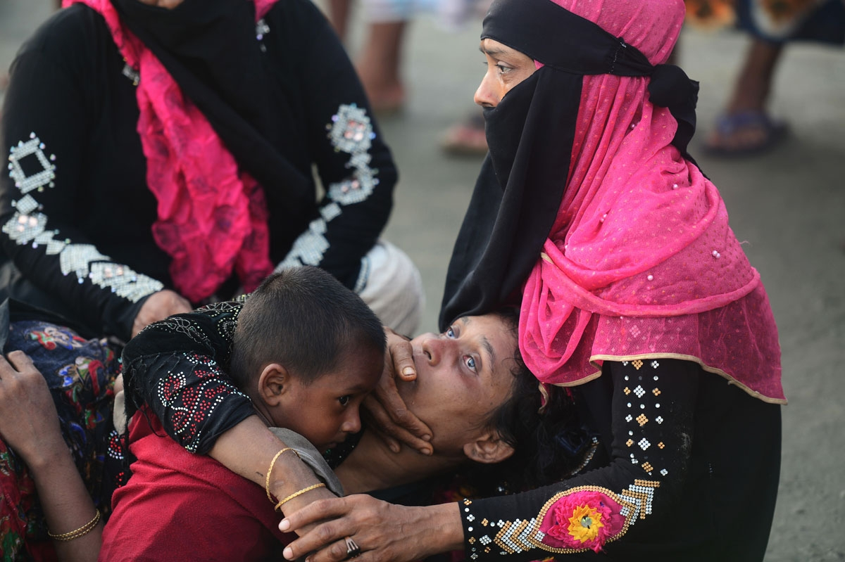 Relatives of a Rohingya refugee comfort her after crossing the border from Myanmar by boat, on the Bangladeshi shore of the Naf river in Teknaf on September 14, 2017.