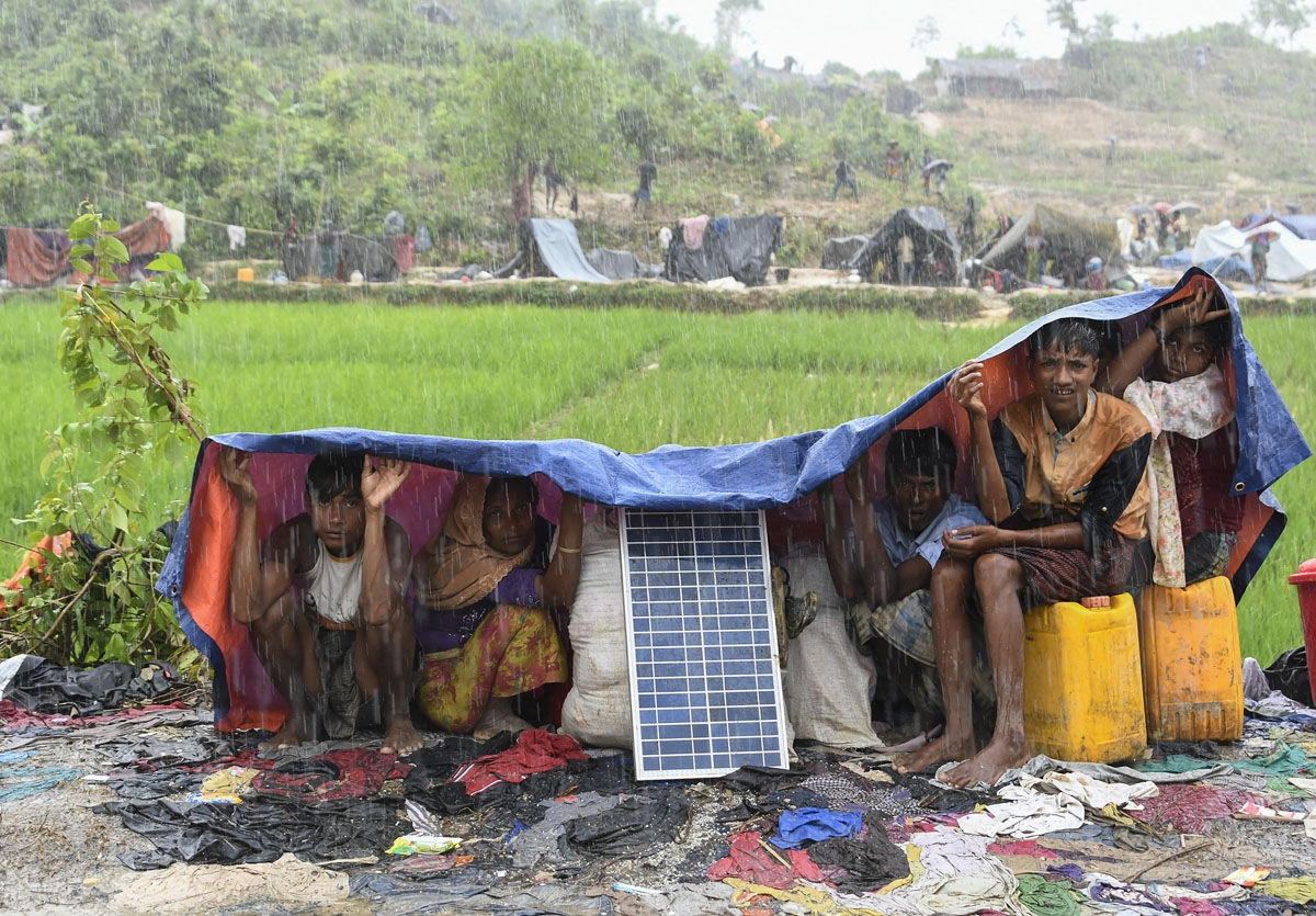 Rohingya refugees protect themself from the rain in Bangladesh's Balukhali refugee camp on September 17, 2017.