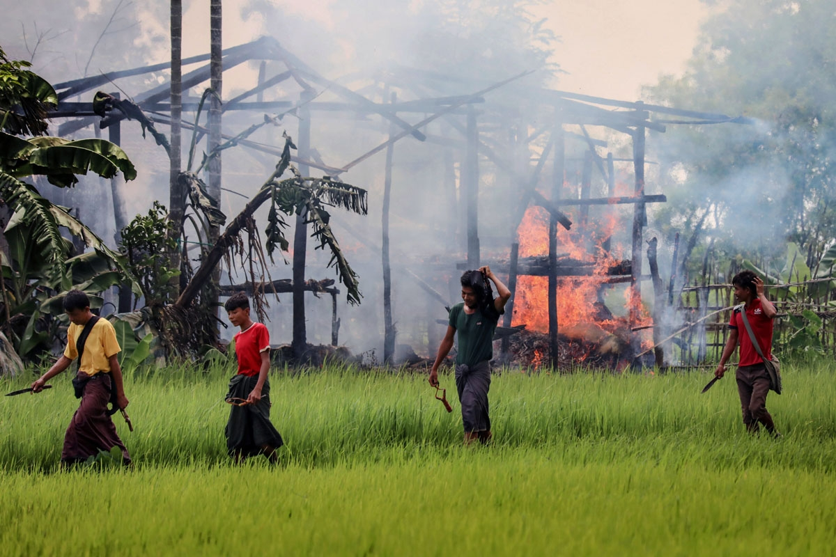 In this photograph taken on September 7, 2017, unidentified men carry knives and slingshots as they walk past a burning house in Gawdu Tharya village near Maungdaw in Rakhine state in northern Myanmar.