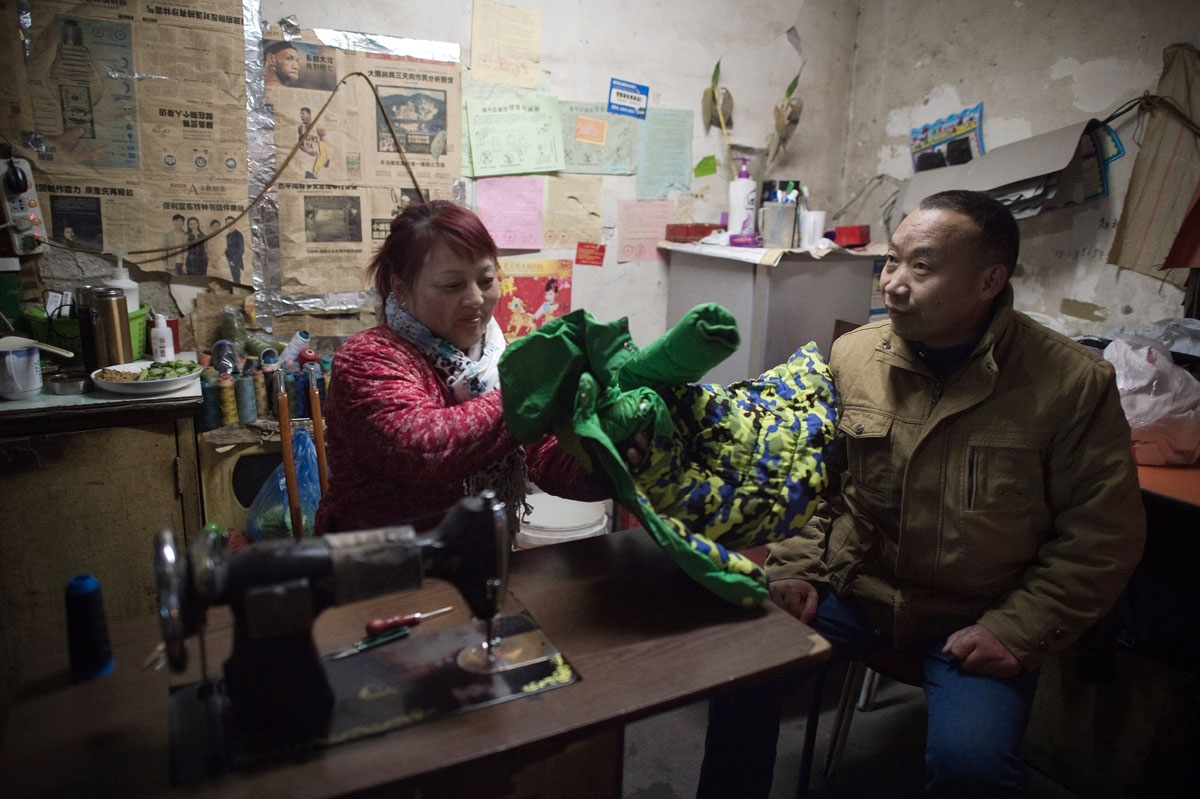 This picture taken on February 16, 2017 shows a customer (R) waiting for his clothes to be repaired in a shop in the Heiqiaocun migrant village in Beijing.