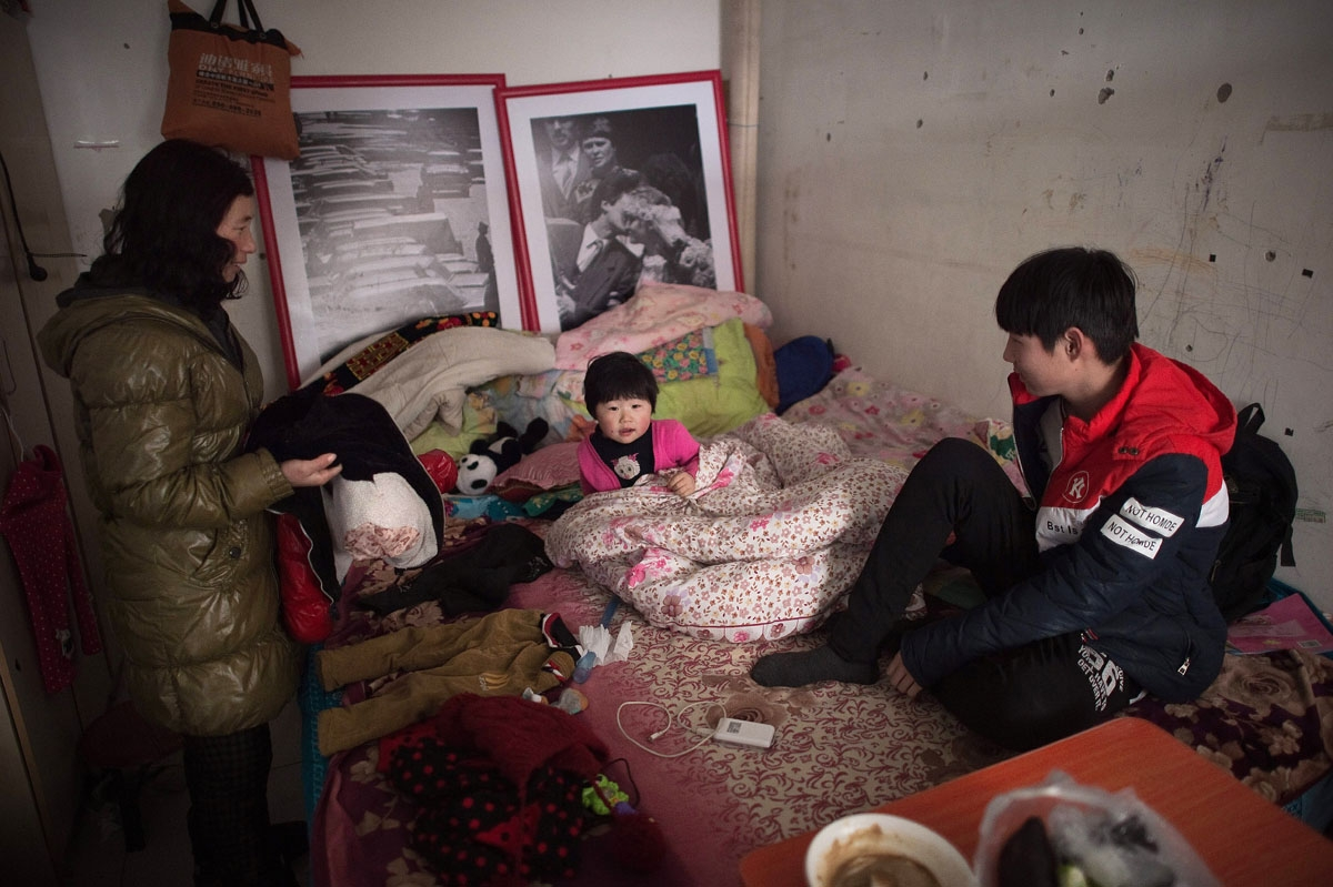 This picture taken on January 18, 2017 shows a family inside their tiny shared room in the Heiqiaocun migrant village in Beijing.