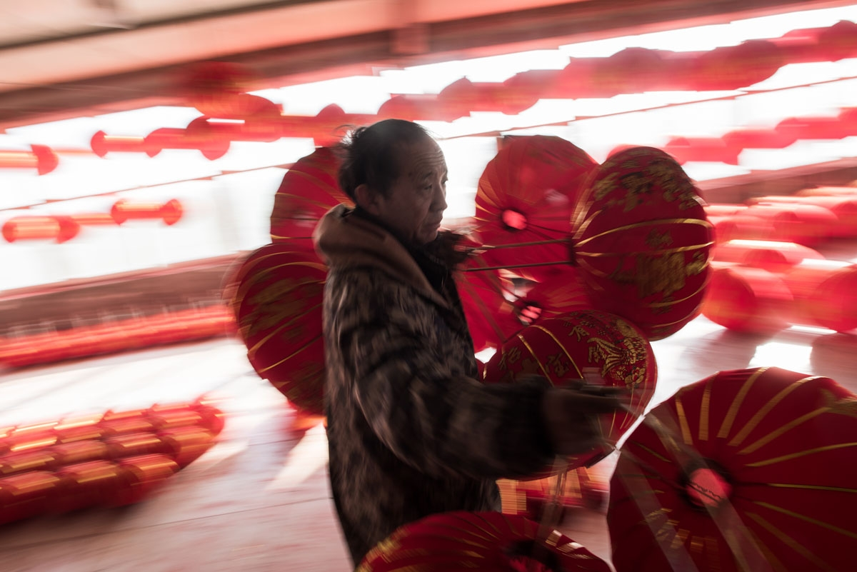 In this picture taken on January 11, 2018 a Chinese worker carries red lanterns for the upcoming Lunar New Year celebrations on February 15, at a factory in the village of Tuntou, in Hebei province southwest of Beijing.