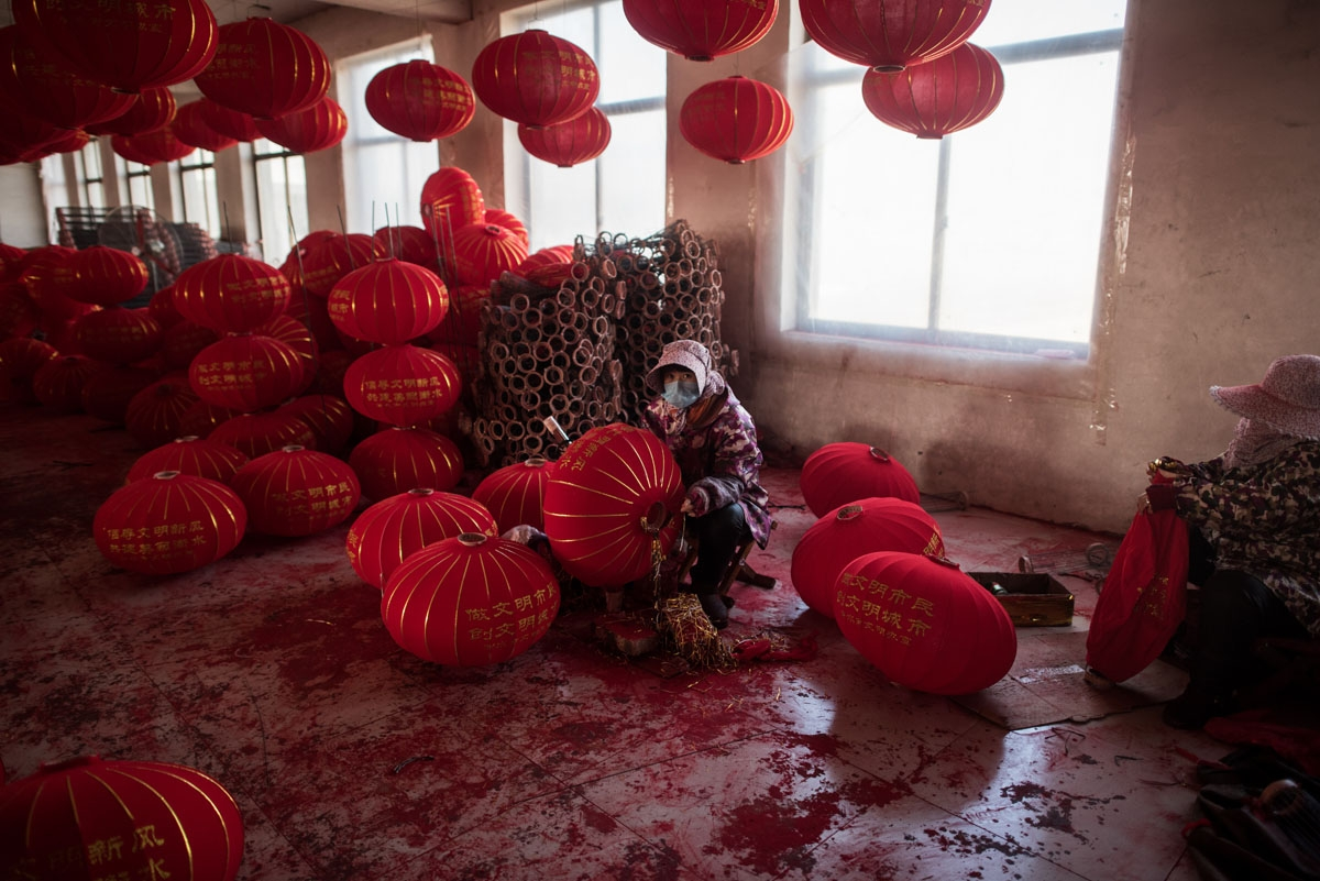 In this picture taken on January 11, 2018 a Chinese worker makes red lanterns ahead of the upcoming Lunar New Year celebrations on February 15, at a factory in the village of Tuntou in Hebei province southwest of Beijing.