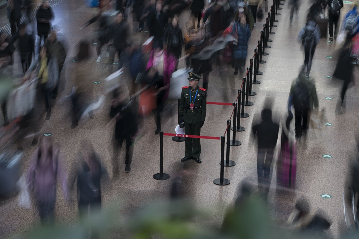 This photo taken on February 10, 2018 shows a Chinese soldier standing in the main hall while travellers rush before boarding trains at the West Railway Station in Beijing, as people depart the capital ahead of the Lunar New Year.