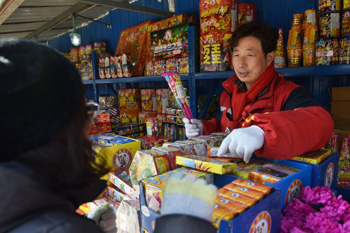 A woman buys firworks at a stall on the outskirts of Beijing in the build-up to Lunar New Year celebrations on February 13, 2018. Beijing has banned fireworks in central city areas during the Lunar New Year holiday in an effort to reduce air pollution and