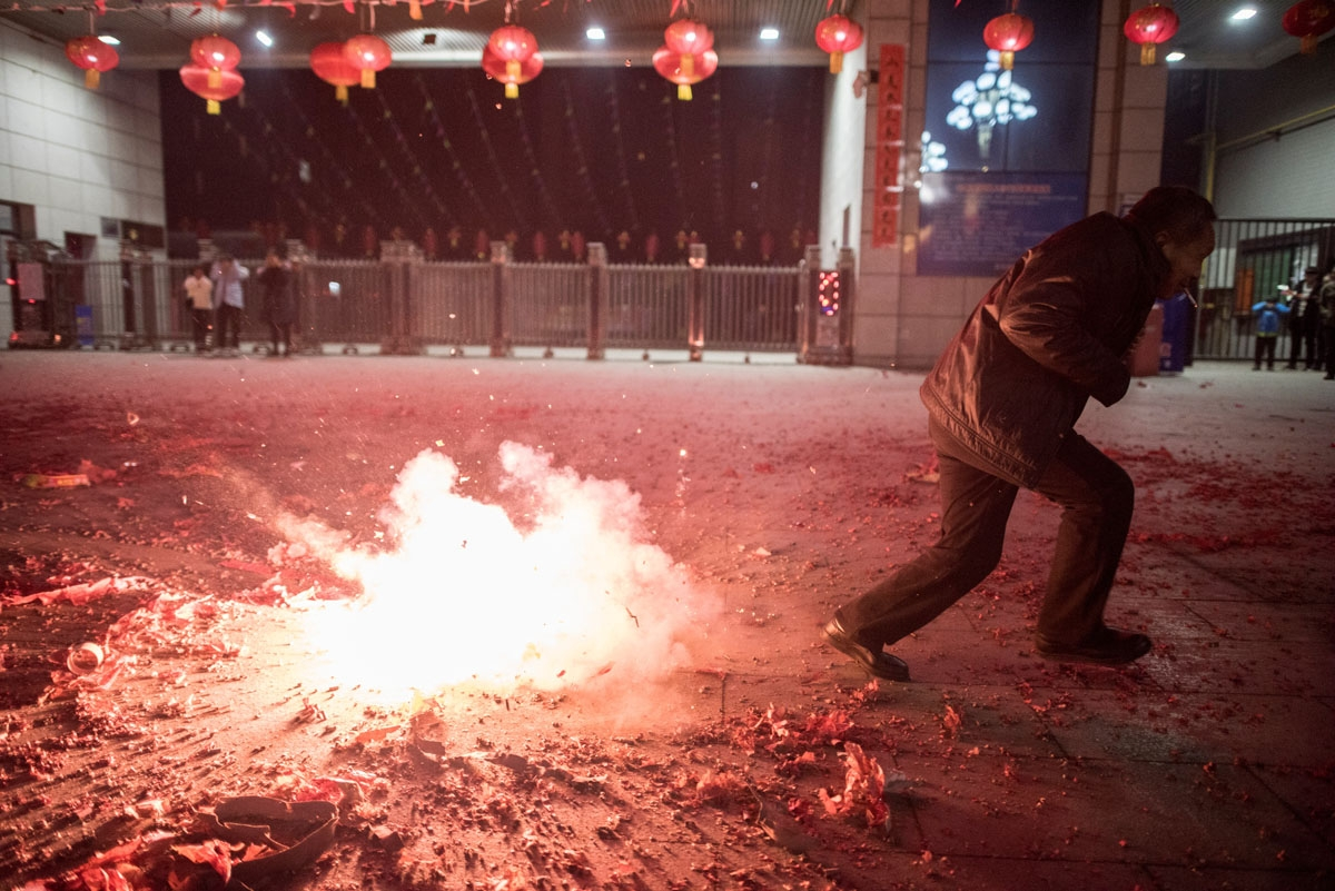 People light fireworks after midnight to celebrate the Lunar New Year, marking the Year of the Dog, in Hancheng, Shaanxi province, on February 16, 2018.