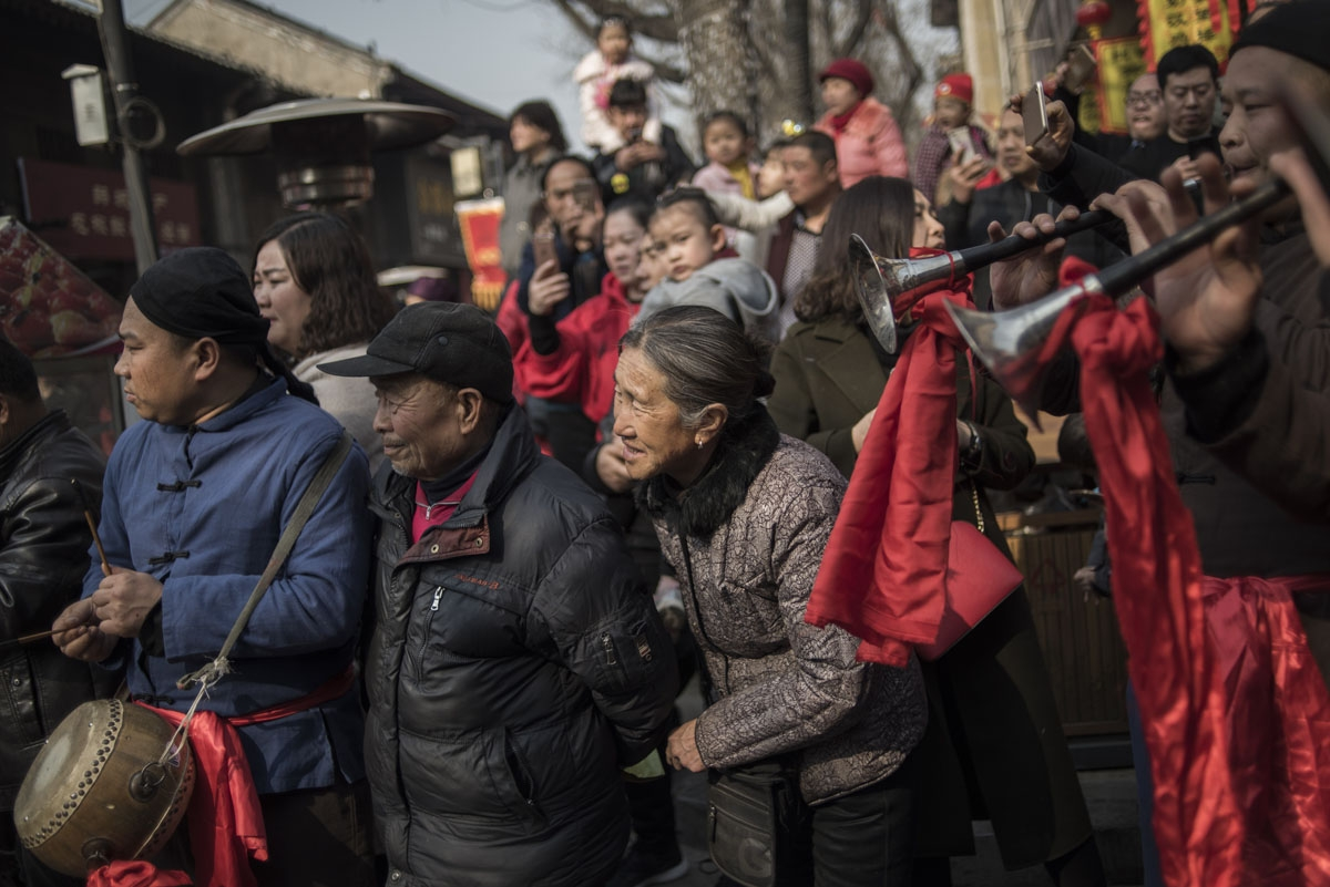 Chinese tourists look at a wedding performance as part of the She Huo festival, to celebrate the Lunar New Year, marking the Year of the Dog, in Hancheng, Shaanxi province, on February 16, 2018.