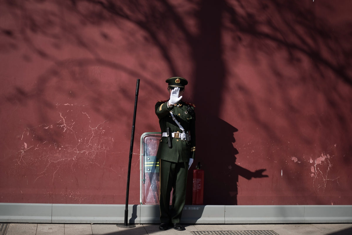 A paramilitary guard gestures not to be photographed at the gate of the Forbidden City ahead of upcoming opening sessions of the Chinese People's Political Consultative Conference (CPPCC) and the National People's Congress (NPC) in Beijing on March 1, 201
