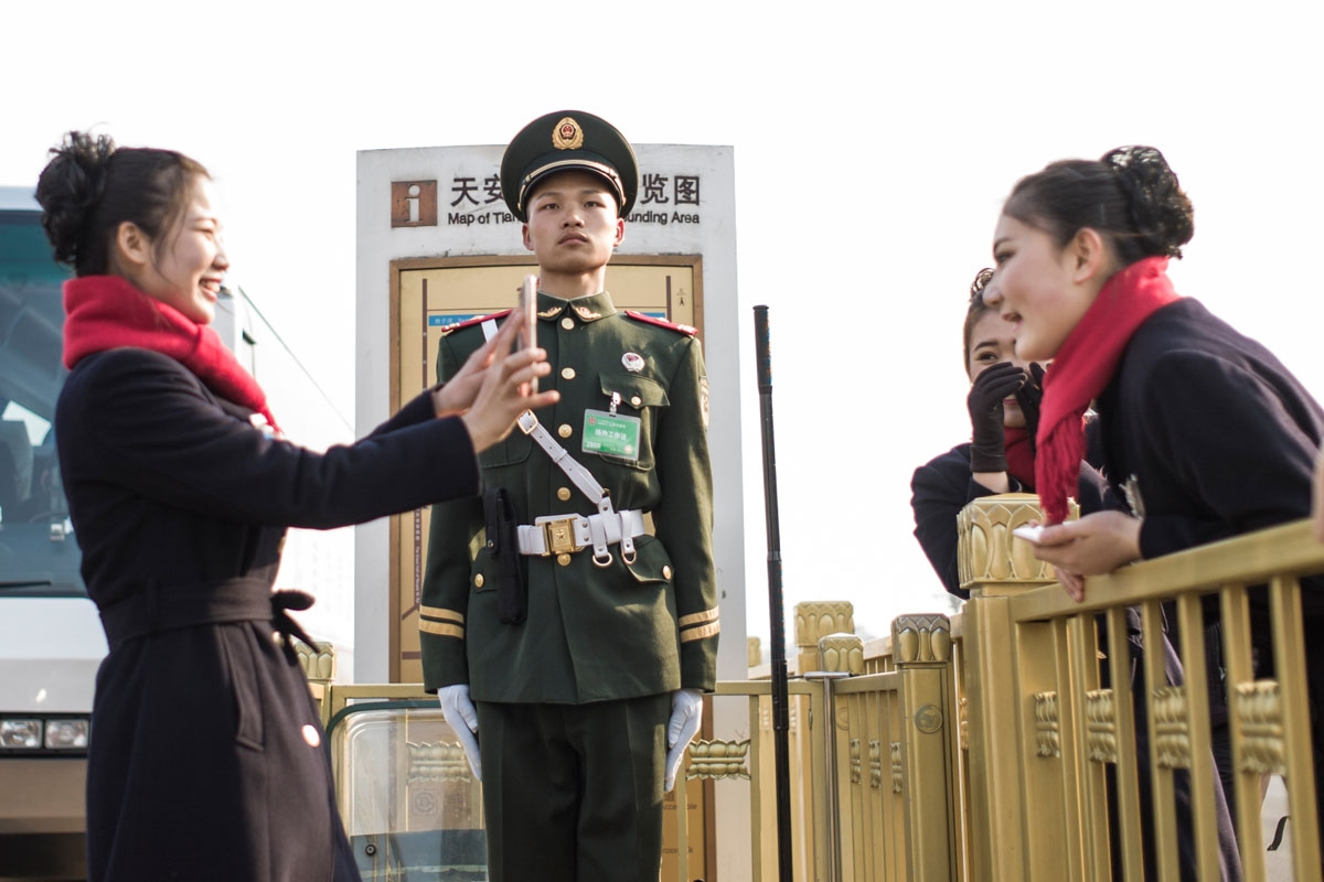 Hostesses take pictures next to a paramilitary guard during the opening session of the Chinese People's Political Consultative Conference (CPPCC) in the Great Hall of the People in Beijing on March 3, 2017.