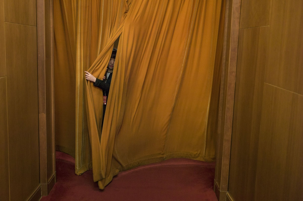 A delegate pulls the curtain to go to the second plenary session of the National People's Congress, China's legislature, at the Great Hall of the People in Beijing on March 8, 2017.