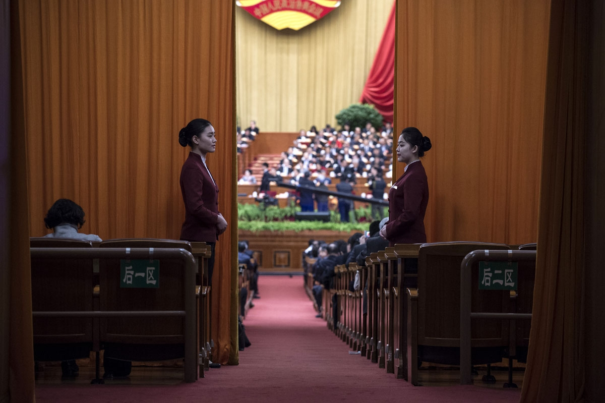 Hostesses stand at the entrance of the Chinese People's Political Consultative Conference plenary session at the Great Hall of the People in Beijing on March 9, 2017.