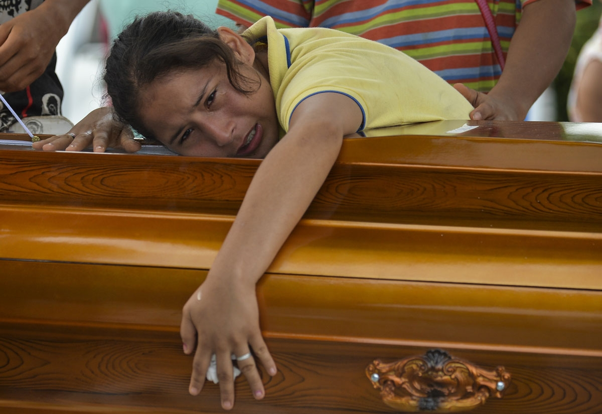 A woman mourns over the coffin of her father killed by a mudslide caused by heavy rains, at the cemetery in Mocoa, Putumayo department, Colombia on April 3, 2017.