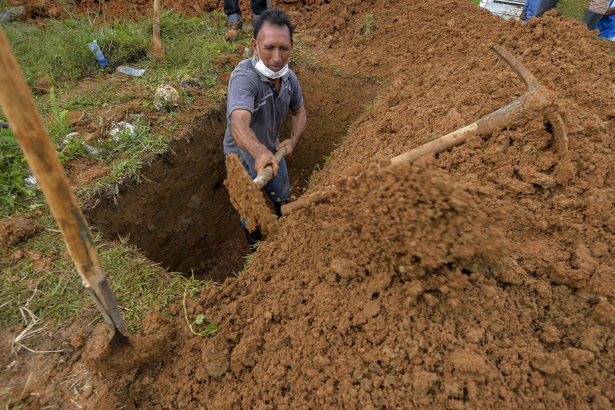 A man digs a grave of a relative killed by mudslides caused by heavy rains, at the cemetery in Mocoa, Putumayo department, Colombia on April 3, 2017.