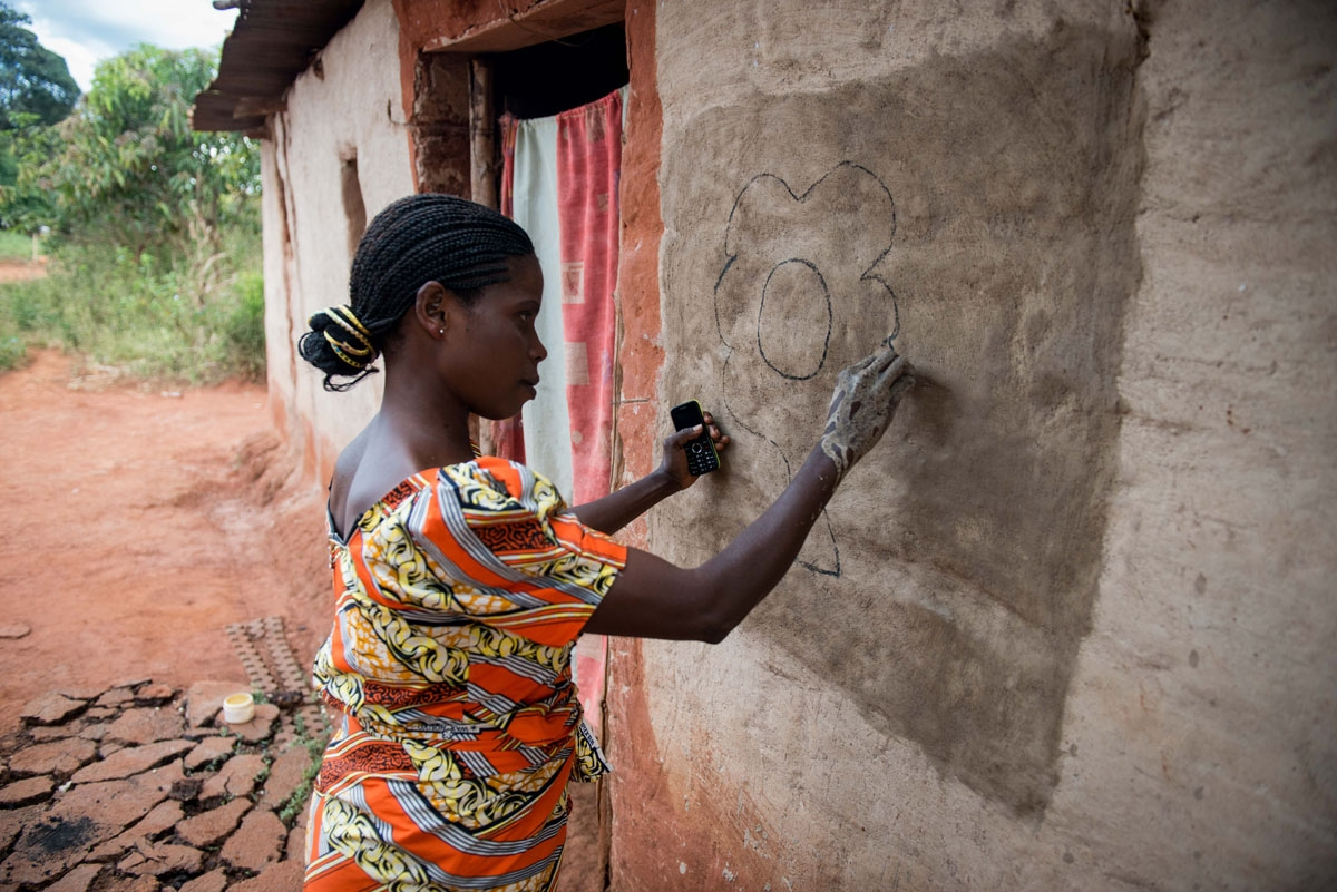 This photograph taken on May 13, 2017, shows villager Josephine Muloba painting a hut with her hands in Makwatsha, DR Congo.