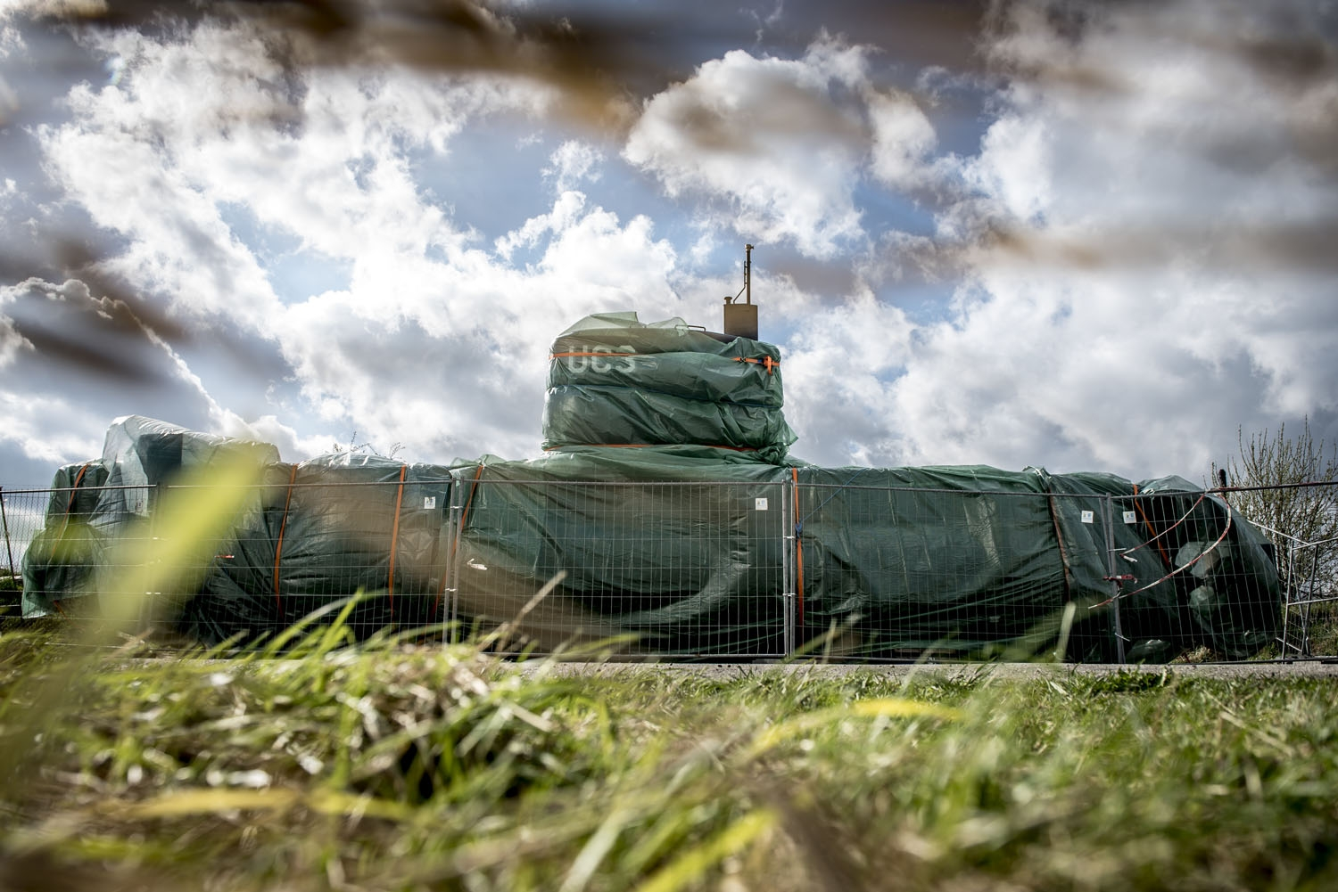 A picture taken on April 25, 2018 shows the homemade submarine UC3 Nautilus as it is covered with green tarpaulin in Nordhavn, a harbour area in Copenhagen, Denmark.
