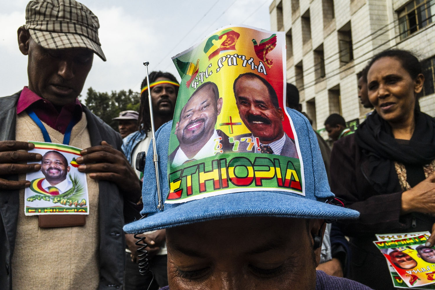 A man wears a hat with the photos of the Eritrean President and the Ethiopian Prime Minister, as people celebrate the arrival of Eritrean President in Addis Ababa on July 14, 2018.