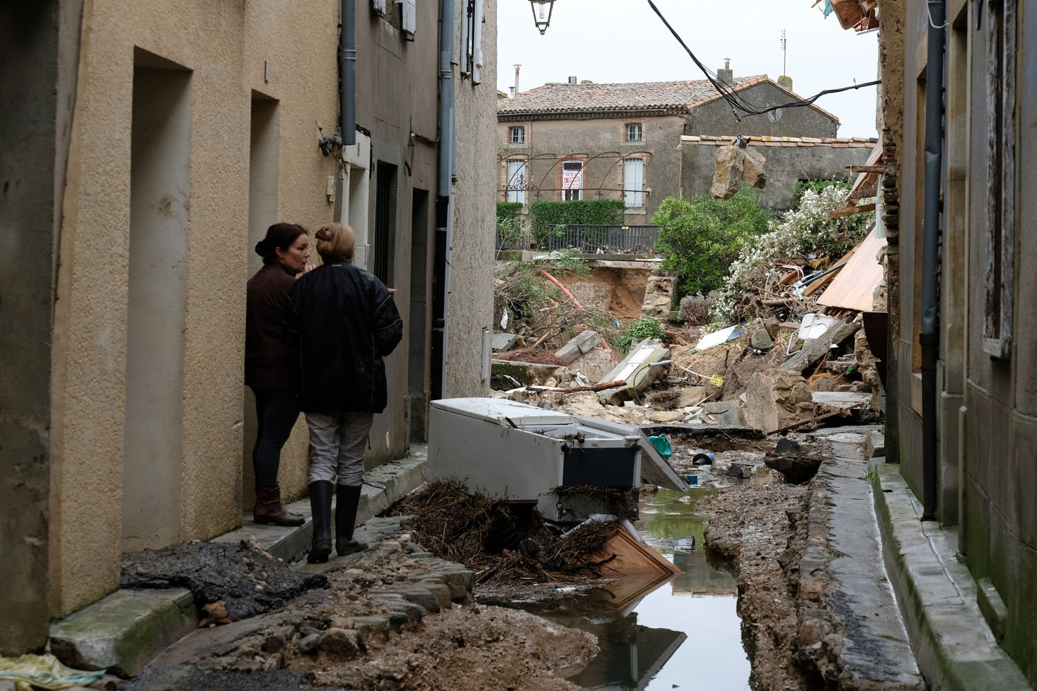 Residents look at the damaged on October 15, 2018 in Villegailhenc, after flash floods swamped a number of towns and villages around the fortress city of Carcassonne, southern France. -