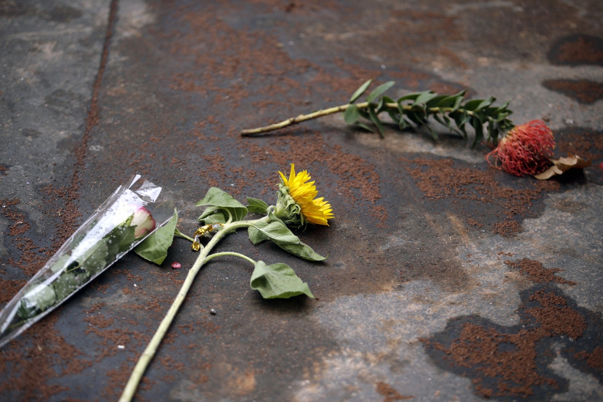 Flowers are put on the sand covering bloodstains on the ground on November 17, 2015, near the the cafe A la Bonne Biere and restaurant Casa Nostra, at one of the sites of terror attacks claimed by Islamic State which killed at least 129 people and left mo